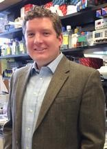 Stephen Parker poses in front of shelves full of lab materials