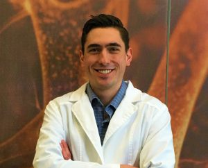 Salatino stands in a lab coat with his arms crossed with an orange backdrop