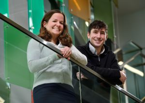 Erin Purcell and Joey Salatino stand with their arms resting against a banister, looking down at the photographer