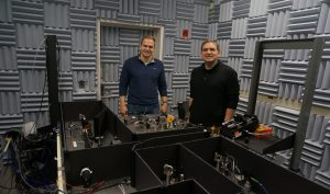 Image of Jens Schmidt and Matthew Comstock stand behind a table on which the optical tweezers sit.