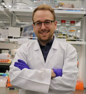 Cort Thompson stands in the lab dressed in a lab coat with his arms crossed