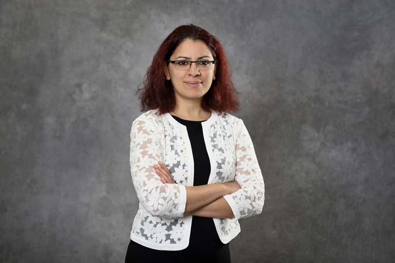 Portrait of Ripla Arora standing in front of a grey backdrop with her arms crossed.