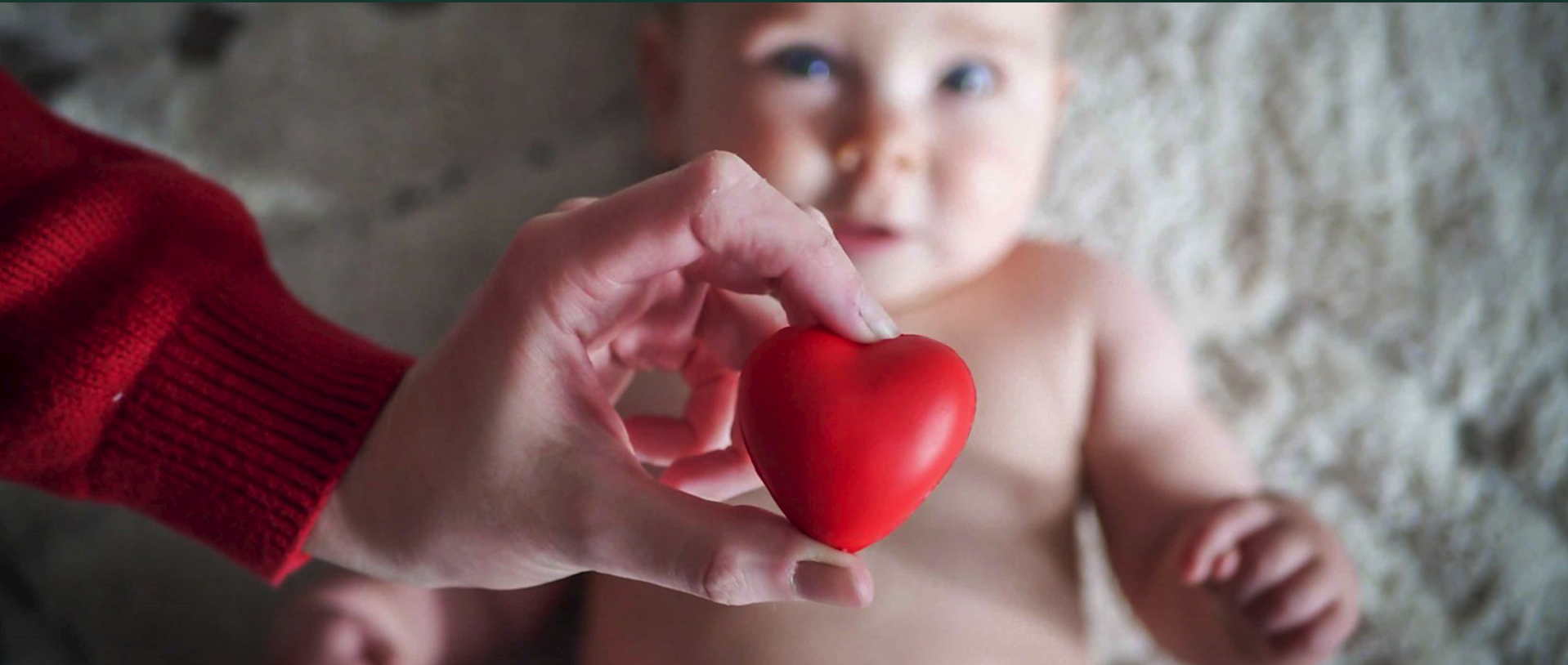 A baby lays down with a person's hand holding a rubber heart over it.
